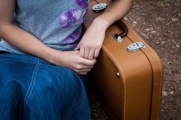 ילדה נשענת על מזוודה